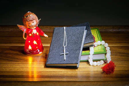 bible altar: Christian books with a cross, beads and a figure of an angel on a wooden table