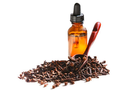 Dried cloves in scoop with essential oil in a bottle. White background