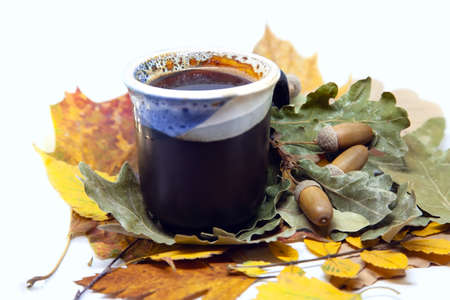 Cup of coffee from roasted acorns on autumn leaves background