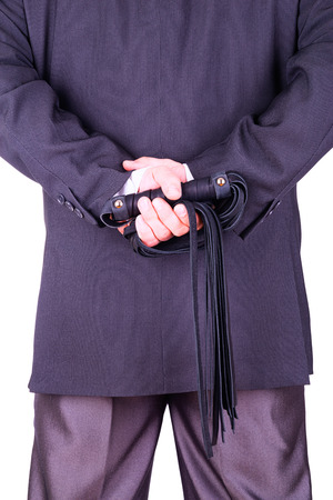 Businessman holding a leather whip.