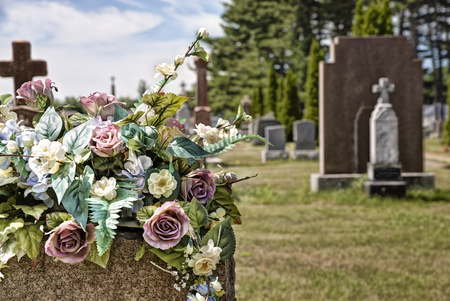 headstones: Flowers on a headstones in a cemetery, bokeh effect in background. Stock Photo