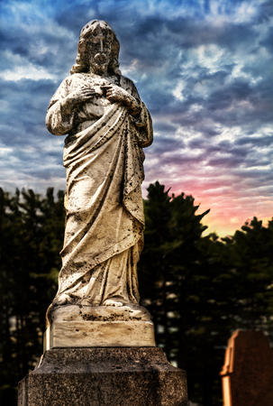 Jesus statue in cemetery, sunset in background.