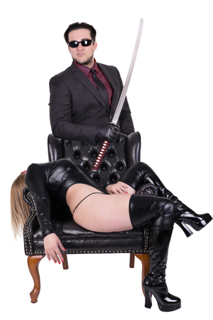 Dangerous killer with katana and woman lying down in chair, isolated on white background.
