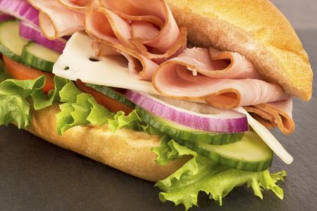 disposed: Close up on submarine ham sandwich, disposed on grey slate.