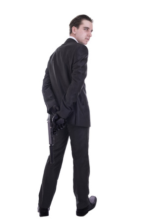 Handsome young man holding gun. Isolated on white background.