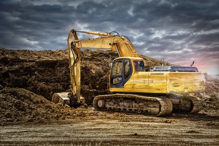 Excavator machinery at construction site, cloudy sky in background.