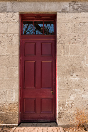 Dark red wooden entrance door. Front view.
