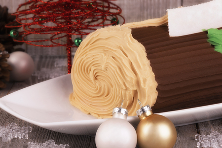 Chocolate yule log cake with Christmas decorations disposed on wooden table.