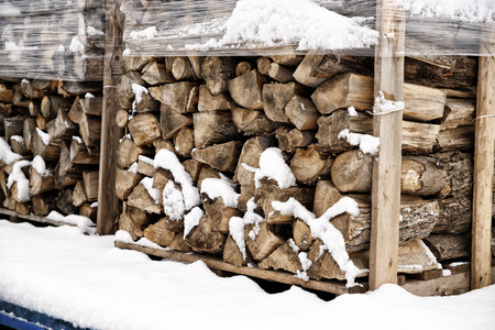 Stack of chopped firewood, covered in winter snow. Wood cut and drying, ready to burn in fireplace. Stock fotó