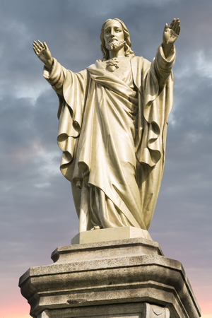 Jesus Christ statue with cloudy sky and sunrise in background.