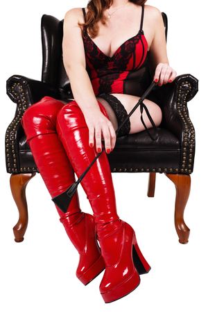 Sexy dominatrix holding crop riding, isolated on white background.