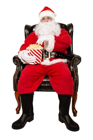 Santa Claus sits in chair is eating popcorn, isolated on white background.