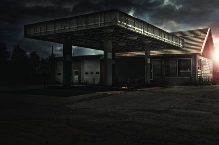 Abandoned freaking old gas station, sunset in background. Banque d'images