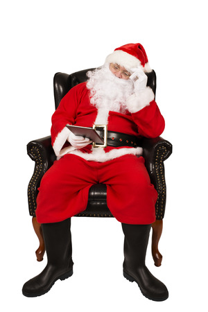 Santa Claus is holding a digital tablet. Photo concept for Christmas holidays.