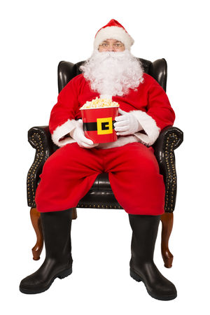 Santa Claus sitting in chair is eating popcorn, isolated on white background.