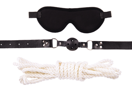 Blindfold mask, rope and a ball gag, isolated on white background.