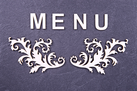 Close up on menu board, directly above. Letters and design made with wood material.