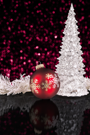 Iced Christmas tree and red bauble on mirror surface with reflection. Black color and bokeh lights in background. Stock Photo