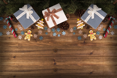 Gift boxes and decoration under Christmas tree, wooden plank in background, directly above. 免版税图像