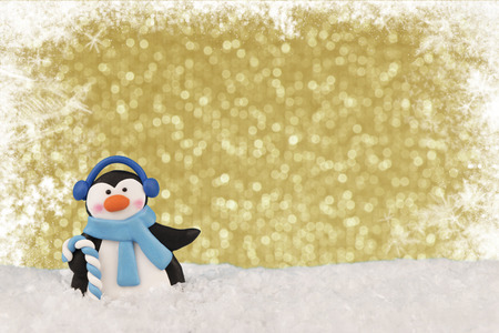 Close up on a dancing penguin, blue bokeh lights in background and snowflakes in border. Christmas greeting card concept.