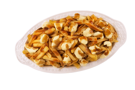 Poutine plate isolated on white background, top view. Cooked with french fries, beef gravy and curd cheese. Canadian cuisine. 免版税图像
