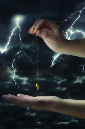 Close up of womans hand holding a pendulum over her palm. Thunderstorm at night in background.