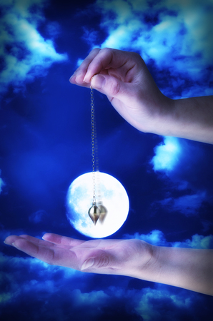 Close up of womans hand holding a pendulum in motion over her palm. Full moon in background.