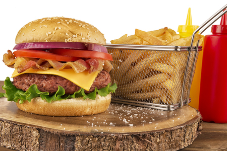 Cheeseburger with beef patty and bacon. French fries in basket, ketchup and mustard bottle in background. Isolated on white background. Real close up.