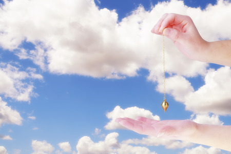 Close up of woman hand holding a pendulum over her palm. Blue sky and white clouds in background.