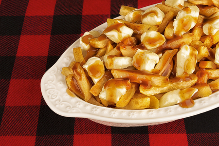 Poutine plate on a red and black tartan tablecloth. Meal cooked with french fries, beef gravy and curd cheese. Canadian cuisine.
