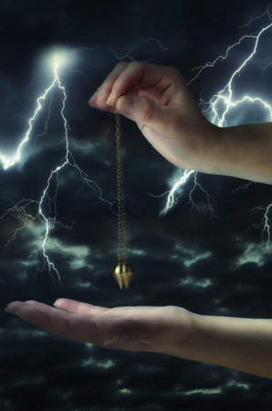 Close up of womans hand holding a pendulum in motion over her palm. Thunderstorm at night in background. Stock Photo