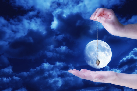 Close up of womans hand holding a pendulum over her palm. Cloudy sky and full moon at night in background. Stock Photo