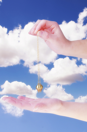 Close up of womans hand holding a pendulum in motion over her palm. Blue sky and white clouds in background.