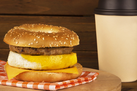 Breakfast sandwich with wooden plank in background. Bagel, egg, cheese, and sausage. Stock Photo