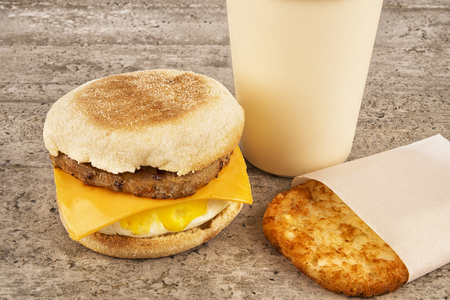 Breakfast sandwich with coffee and hash brown on concrete table. English muffin, egg, cheese and sausage. Banque d'images