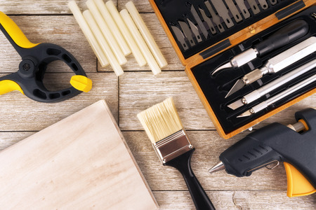Set of DIY tools on a white wooden plank, directly above. Glue gun, paint brush, clamp and precision knives.