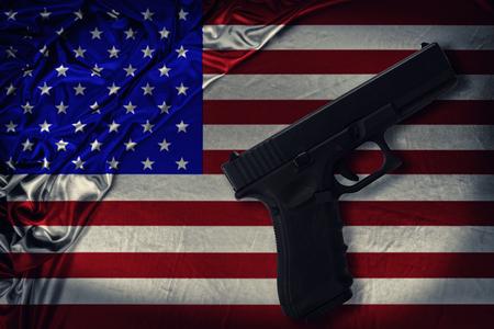 Arma de fuego dispuesta en diagonal sobre una bandera de los Estados Unidos de América. Directamente arriba. Foto de archivo