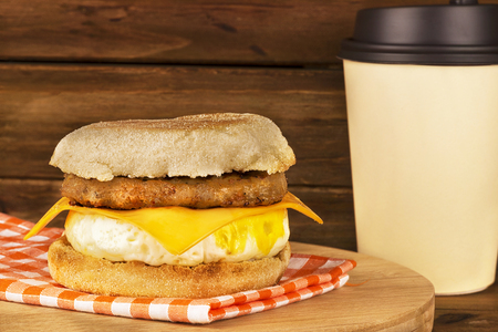 Sandwich breakfast with wooden plank in background. English muffin, egg, cheese, and sausage. Stock Photo
