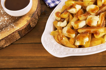 Poutine plate on a wooden background. Cooked with french fries, gravy and curd cheese. Canadian cuisine.