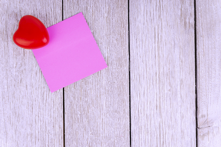 Pink paper notepad on white wooden plank in background. Copy space for text.