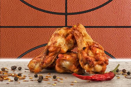 Chicken wings with red hot chili pepper, salt and peppercorn. Basketball ball image in background.