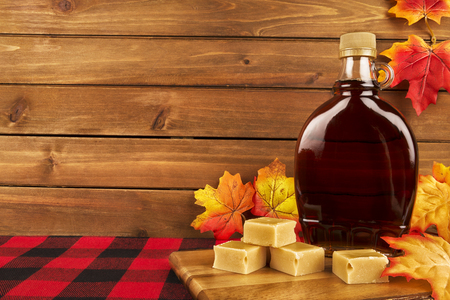 Maple syrup bottle on a wooden plank. Maple leaves in decoration. Copy space for your text. Reklamní fotografie