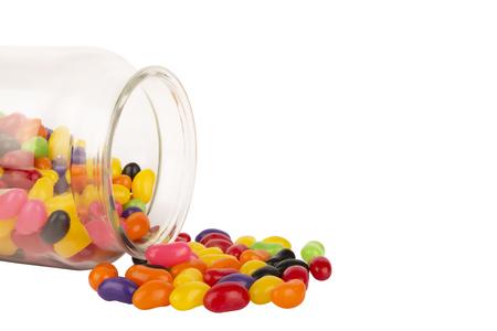 Piccolo barattolo di vetro con i fagioli di gelatina colorati sparsi isolati su fondo bianco. Copia spazio per il tuo testo. Archivio Fotografico