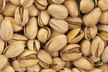 Top view on a stack of salty pistachio nuts as abstract background. Copy space for your text. Imagens