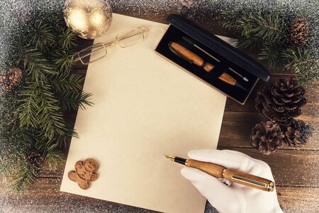 Santa Claus writing a letter, directly above. Flat lay for Christmas concept