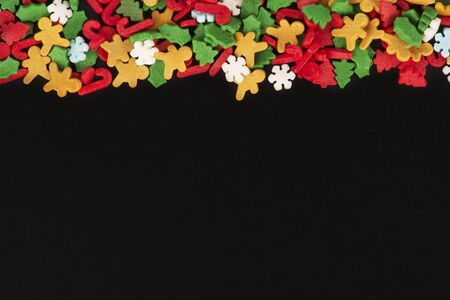 Christmas candies for pastry decoration on a blackboard. Directly above. Copy space for your text.
