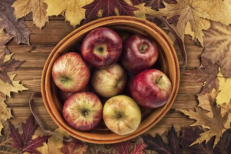 Apples basket and maple leaves disposed on a wooden table. Flat lay, top view of autumn decoration concept.