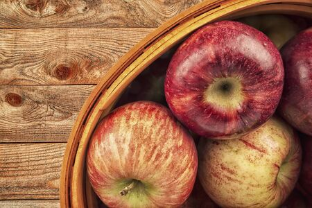 Apples basket disposed on a wooden table. Flat lay, top view of autumn decoration concept. Stok Fotoğraf