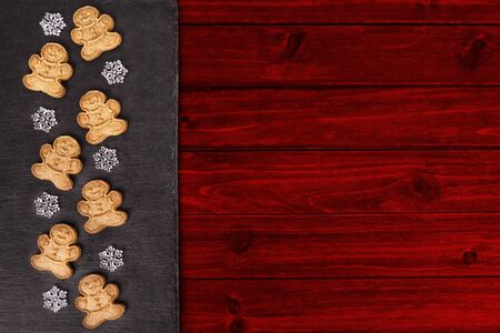 Gingerbread cookies and snowflakes in decoration on red wooden table, directly above. Stok Fotoğraf