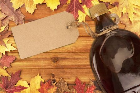 Maple syrup bottle with an empty label on a wooden plank. Maple leaves in decoration. Copy space for your text.